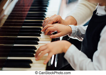 experienced master piano hand helps the student -...