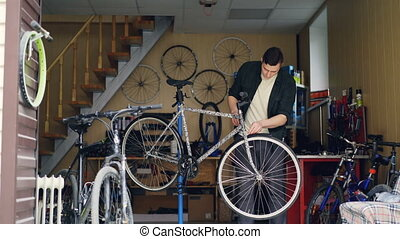 Experienced mechanic in casual clothes is checking handlebar...