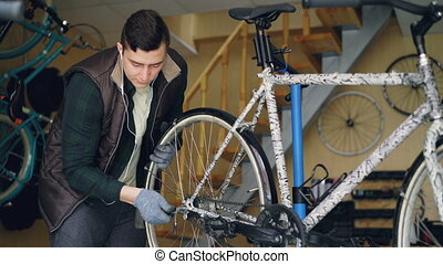 Experienced mechanic is assembling bicycle adjusting back...