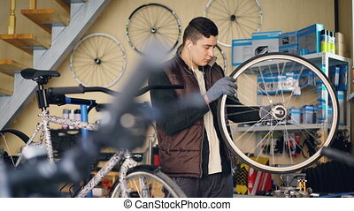 Experienced mechanic is rotating bicycle wheel checking work of mechanism and listening to music while working in small workshop. Maintenance and people concept.