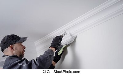 experienced painter is coloring plinth, fixing between...