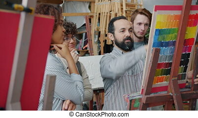 Experienced painter teaching group of students drawing and ...