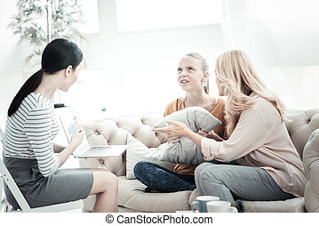 Experienced phycologist having conversation with mom and daughter