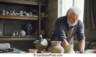 Experienced potter is kneading clay with his hands on...