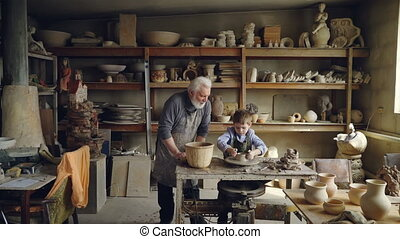 Experienced potter loving prandparent is teaching his grandchild pottery in small home workshop. Boy is working with throwing wheel, grandpa is talking to him.