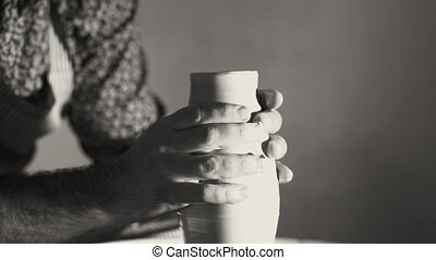 Experienced potter shapes the clay product - jug - with...