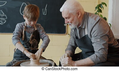 Experienced potter teaching boy to work with spinning wheel ...