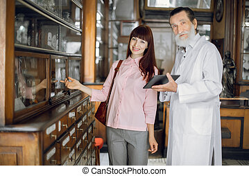 Experienced professional man pharmacist holds tablet and consults smiling female customer in old ancient pharmacy. Pharmacist and patient compliance concept