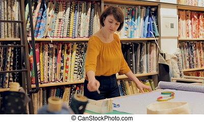 saleswoman arranging fabric bolts in textile shop, preparing...