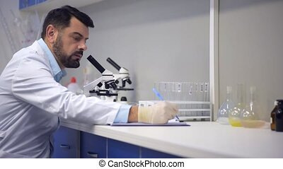 Experienced scientist in labcoat looking through microscope and taking notes