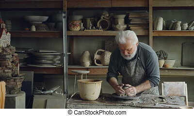 Experienced sculptor senior adult is making sculpture from...