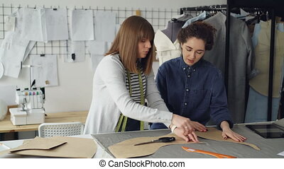 Experienced seamstress is teaching her assistant to outline clothing patterns on fabric. Young woman is focused on process, watching carefully and asking questions.