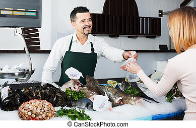 Experienced seller in fishery - Mature seller standing near ...