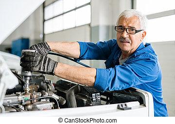 Experienced senior technical engineer in eyeglasses looking at you during work