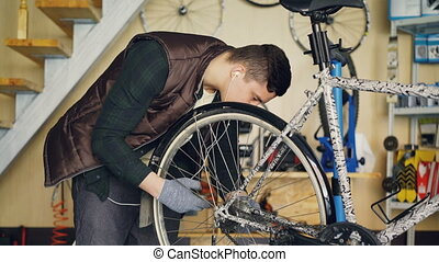 Experienced serviceman is assembling bicycle adjusting back...