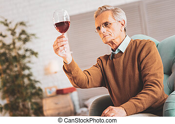 Experienced sommelier checking French red wine