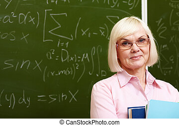 Experienced teacher - Charming older woman posing with a ...