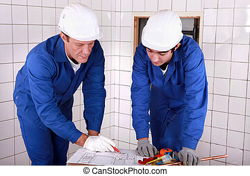 Experienced tradesman teaching his apprentice how to read a...