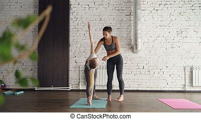 Experienced yoga teacher is demonstrating extended triangle...