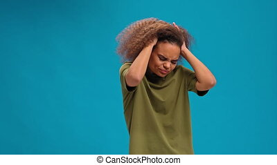 Experiencing migraine or headache African American young woman standing holding head with hands in olive t shirt isolated on blue background. Human emotions, facial expression concept.