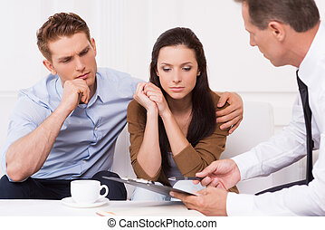 Expert advice. Thoughtful young couple sitting on the couch while confident financial advisor explaining something and pointing clipboard