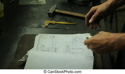expert checks the item after the repair on workplace, opens recording details and scrolls the magazine in his hands detail on the table are a number of locksmith tools.