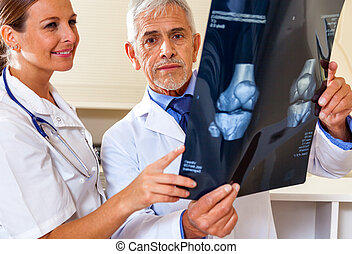 Expert doctor analyzing x-ray scan with female assistant