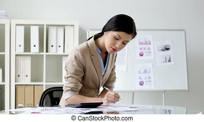 Expert - Female accountant making calculations and reviewing...