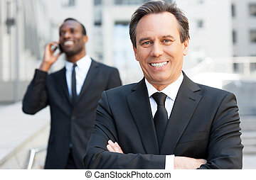 Expert in business world. Confident senior man in formalwear keeping arms crossed and smiling while African man talking on the mobile phone in the background