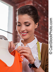 Expert in fashion industry. Low angle view of beautiful young fashion designer adjusting dress on the mannequin and smiling