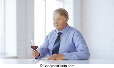 expert in suit and tie with a glass of red wine