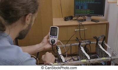 Expert technician using a power meter monitoring and...