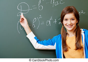 Explaining - Confident student pointing at formula on...