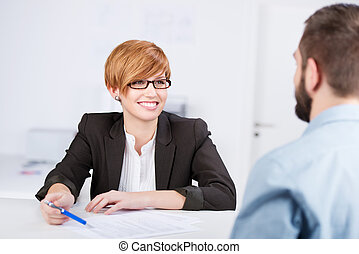 Happy young businesswoman explaining document to male coworker at office desk