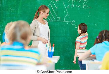 Explaining formula - Portrait of smart teacher standing by...