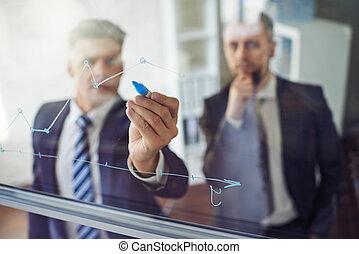Explaining graph - Businessman explaining graph to his...