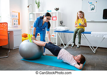 Active little patient stretching whole body while leaning on pilates ball