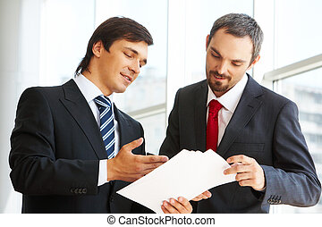 Image of confident businessman looking at document in partner?s hand while discussing it