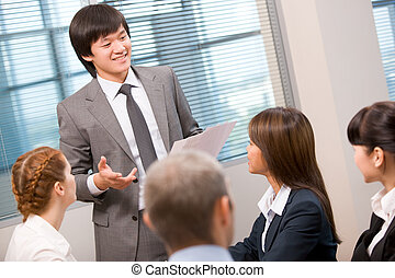 Photo of confident businessman explaining activities to his colleagues in office
