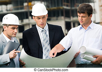 Explanation - Portrait of workgroup of builders looking at...