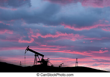 exploited oil field on sunset with silhouettes