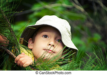 young boy wearing a hat pretending to be an explorer in the woods