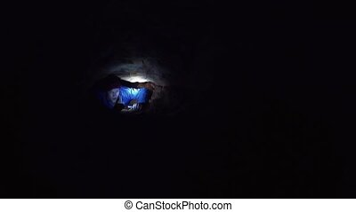 Explorer climbs outward from narrow hole inside cave with...