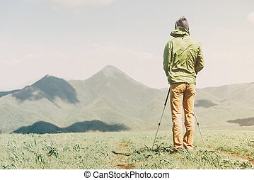 Explorer man with trekking poles in the mountains