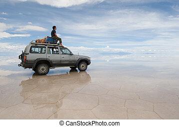 explorer - a man sitting on top of jeep in salt desert