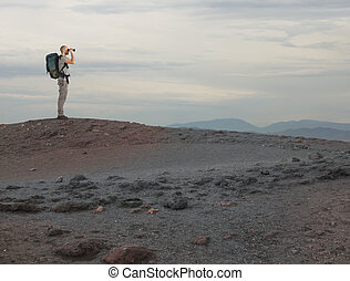 Explorer with binocular searches something in a desert
