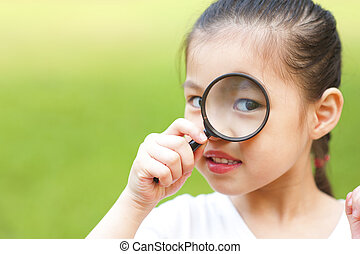 Little girl exploring nature by magnifier