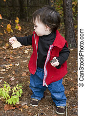 Little girl exploring nature in the fall
