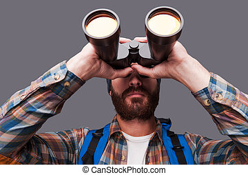 Exploring new places. Confident young bearded man carrying backpack and looking through binoculars while standing against grey background