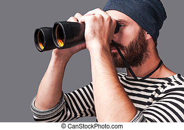 Exploring new places. Side view of confident young bearded man in striped clothing looking through binoculars  while standing against grey background